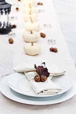 Remember to keep table ornaments simple: you don't want guests at a loss for what to do with their place holders, so insure there is ample room to move décor to the side.